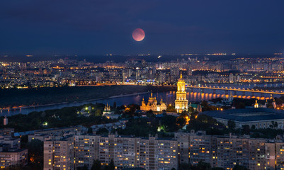 Wall Mural - Kyiv cityscape at night with full moon, Ukraine