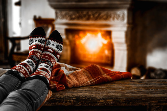 Woman legs with christmas socks and fireplace background in home interior