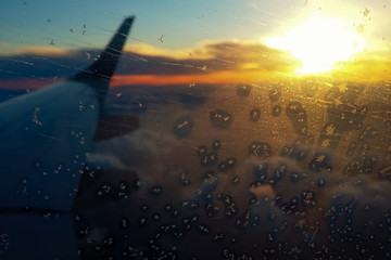 Rime snowflakes on the porthole of an airplane. Sunset in the clouds view from the airplane window porthole. Wing of an airplane in the sunset hoar frost. The effect of film grain.