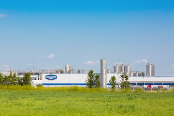 MOSCOW REGION, RUSSIA - AUGUST, 2017: Danone factory in Russia with green grass and blue sky