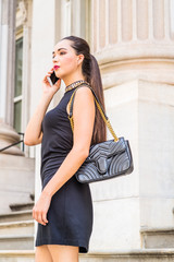 Young South American Businesswoman working in New York City, wearing black sleeveless dress, shoulder carrying leather bag, standing on stairs outside old style office building, talking on cell phone.