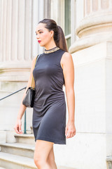 Young American Businesswoman Fashion. Young South American Woman working in New York City, wearing black sleeveless dress, shoulder carrying leather bag, walking down stairs from office building.