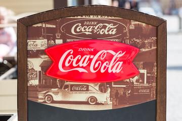 Prague, Czech Republic - April, 2018: Vintage Coca Cola advertisement sign in Prague, Czech Republic. The most famous carbonated soft refreshment drink in the world.