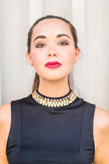 Portrait of South American Female College Student in New York City. Young Beautiful Hispanic Woman wearing black sleeveless dress, standing against column outside office building. Close Up Head Shot.