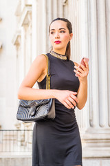 Young South American Businesswoman working in New York City, wearing black sleeveless dress, shoulder carrying leather bag, standing inside old style of office building, holding cell phone, looking..