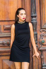 Portrait of South American Female College Student in New York City. Young Beautiful Hispanic Woman wearing black sleeveless dress, standing against brown vintage wooden office door, looking away..
