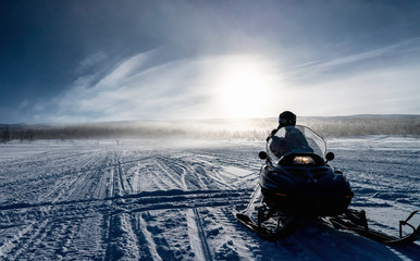 One person ready to drive snowmobile in very cold mountains in Sweden, frosty fog around bright sun creates halo effect, birches forest and mountains behind driver. Hemavan -Tarnaby area, Lappland