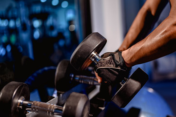 Young men wear sportswear, prepare dumbbell weights for exercise in the gym.