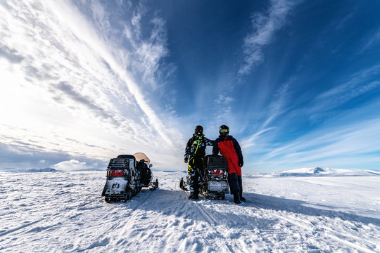 Two snowmobiles (back side) and two friends pose around of one snowmobile. They dressed for driving in cold mountains, waiting to start the holiday adventure. Hemavan, Tarnaby in Lappland, Sweden
