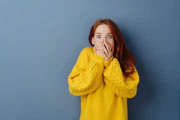 Shocked young woman with hands to mouth