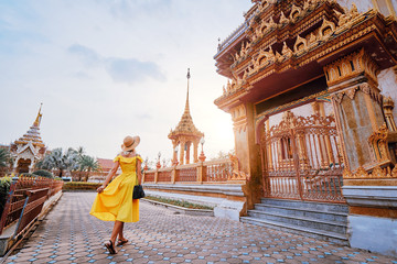 Foto op Plexiglas Bangkok Travel by Asia. Young woman in hat and yellow dress walking near the Chalong buddhist temple on Phuket Island in Thailand.