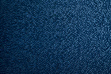 Leather texture close up. Dark blue fashionable background, top view. Stylish wallpaper of snake skin. Rough surface of navy blue color.