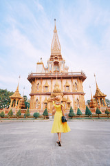 Travel by Asia. Young woman in hat and yellow dress walking near the Chalong buddhist temple on Phuket Island in Thailand.