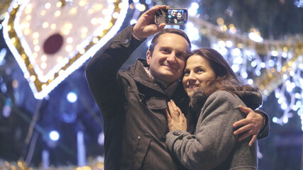 Couple of romantic couple taking selfie at Christmas tree outdoor, kiss