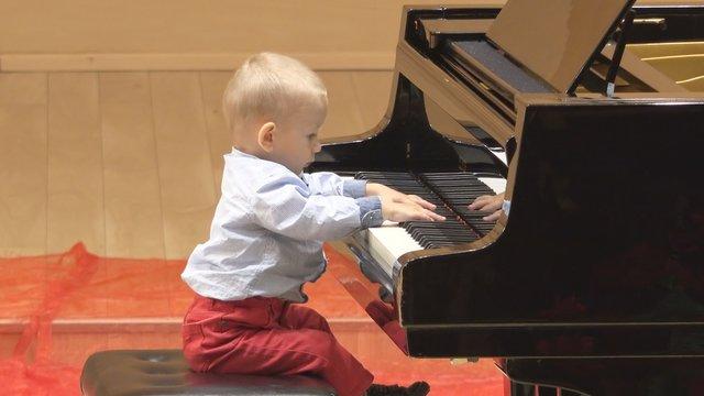 Amusing baby playing at piano, curious looking at musical instrument