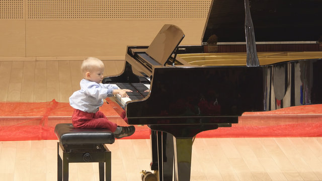 Little child playing at big piano in concert hall, early artistic education
