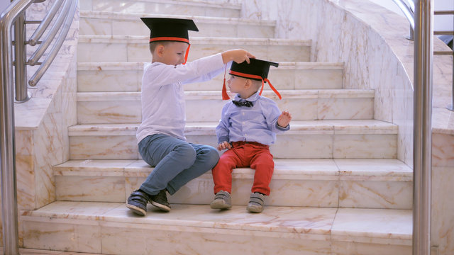 Two children sit on stairs, big brother arrange graduation cap to baby brother