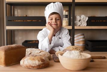 Dreamy little baker working in store