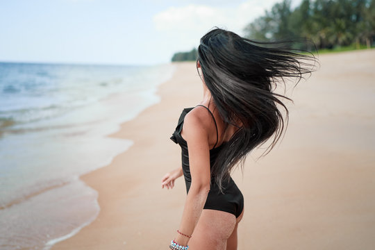 Sexy beauty and beach fashion. Outdoor portrait of beautiful young woman with long hair walking near the sea.