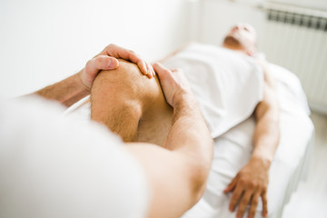 Young man male athlete having sport massage at spa or home by professional therapist relax body recovery healing injury leg knee