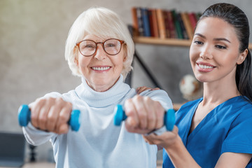 Old woman training with physiotherapist using dumbbells at home