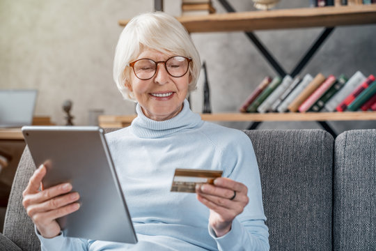 Shopping online. Senior woman using tablet computer and credit card