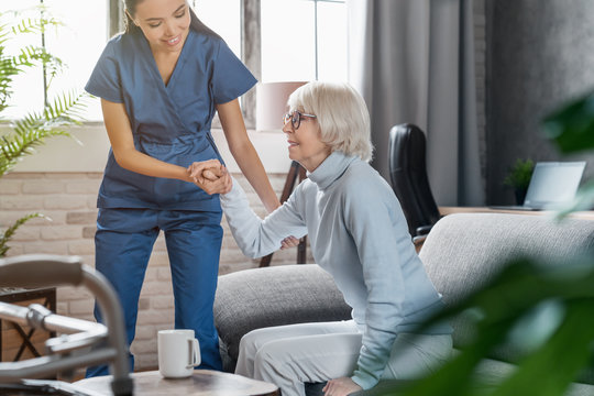 Professional caregiver taking care of elderly woman at home