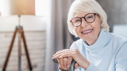 Portrait of happy mature woman in eyeglasses holding cane while sitting on sofa at home Wall mural