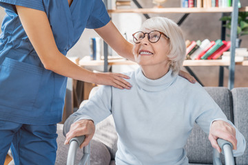Cropped image of female caretaker helping senior woman to walk with walker at home