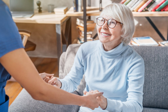 Cropped image of female professional caregiver taking care of elderly woman at home