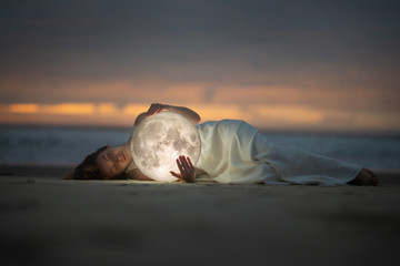 Obraz Astrology. Secret and riddle. Beautiful attractive girl on a night beach with sand hugs the moon, art photo. - fototapety do salonu
