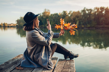 Autumn season. Woman taking photos of branches with leaves using smartphone on river pier