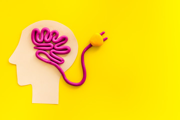 Brain charging and mental rest. Plug and cable leads to plastiline meanders on yellow background top view copy space