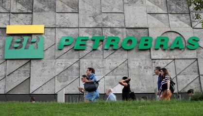 People walk in front of the Brazil's state-run Petrobras oil company headquarters in Rio de Janeiro