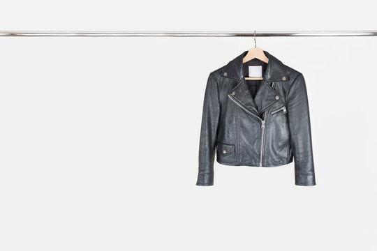 Fashion leather jacket hanging on hanger on white background