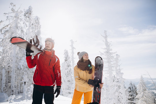 Happy couple having fun time with snowboards. Winter Sport