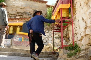 A Tibetan man spins a prayer wheel.