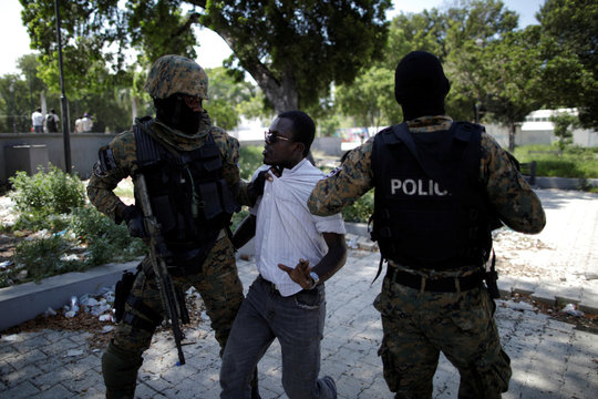 Officers with the National Palace General Security Unit (USGPN) question a man during clashes with protesters as a funeral of two men, organised by the Popular and Democratic Sector, takes part in Port-au-Prince