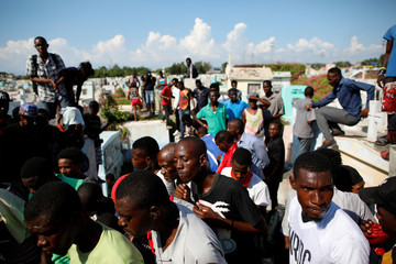 Mourners look at a coffin in the cemetery of Port-au-Prince during a funeral of two men, organised by the Popular and Democratic Sector, in Port-au-Prince