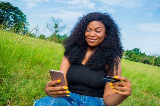 young pretty african lady feeling happy as she is shopping online with her smart phone and holding her credit card