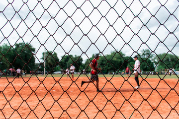 Picture of the softball field being played  That was taken through the net.
