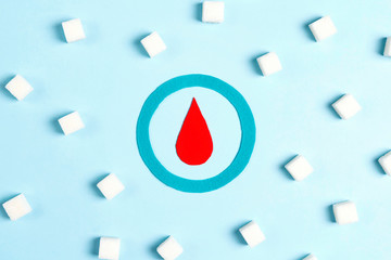 World diabetes day concept with symbol of diabetes and sugar pieces on blue background.