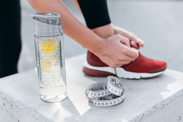 Closeup glass bottle of water with lemon and tape measure