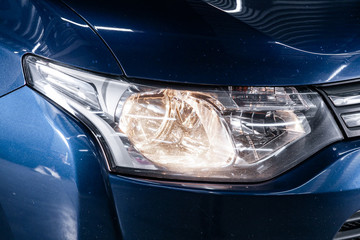 Macro view of modern car xenon lamp headlight, bumper, wheel. Exterior of a modern car.