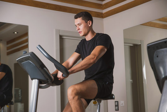An athlete is engaged in the gym, a Young man does cardio on an exercise bike