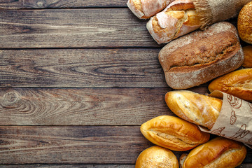 Assortment of baked bread on wooden table background,top view