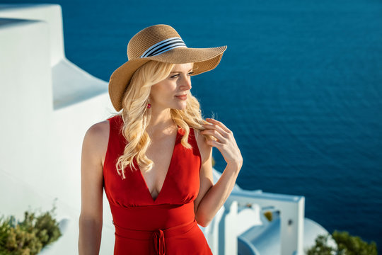 blond woman with a sun hat and a red summer dress in Oia on Santorini, with water in the background
