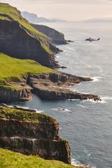 Helicopter flying over mykines atlantic cliffs in Faroe islands. Transportation