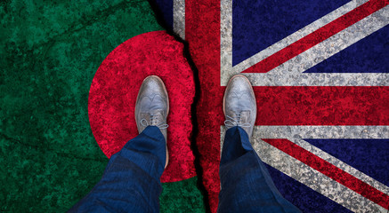 Business man stands on cracked flag of UK and Bangladesh. Political concept