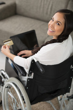 woman in wheelchair making an online purchase on her laptop